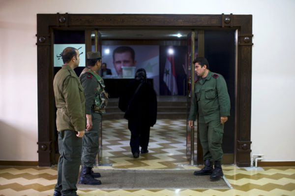 Syrian policemen stand guard outside a polling station during the parliamentary election in Damascus, Syria, Wednesday, April 13, 2016. Polling stations opened in government-held parts of Syria where a new 250-member parliament will be elected. (AP Photo/Hassan Ammar)