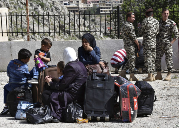 Displaced people who fled the Syrian war sit on their belongings near the Lebanese-Syrian border as they prepare to return to their village of Beit Jinn in Syria, while Lebanese General Security soldiers stand guard, in the southern village of Shebaa, Lebanon, Wednesday, April, 18, 2018. Hundreds of refugees are headed back to Syria in what they say is a voluntary decision to return to homes in the war-torn country. (AP Photo/Ziad Choufi)